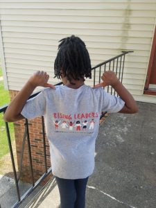 "A young girl shows the back of her Crestwood Summer Camp t-shirt. Text says, ""RISING LEADERS,'"" and underneath is a graphic of girls holding hands surrounded by stars."
