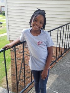 Breana, a young girl, smiles in a gray t-shirt with a red Girls Inc. logo.